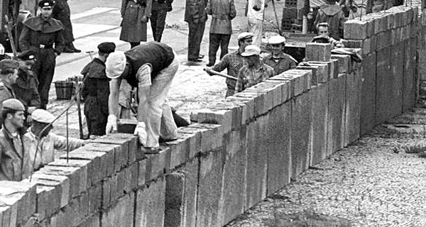 Unter der Aufsicht von bewaffneten Volkspolizisten errichtet eine Ostberliner Maurerkolonne am Potsdamer Platz eine mannshohe Mauer. Quelle: dpa - Bildarchiv. Fotograf: UPI.